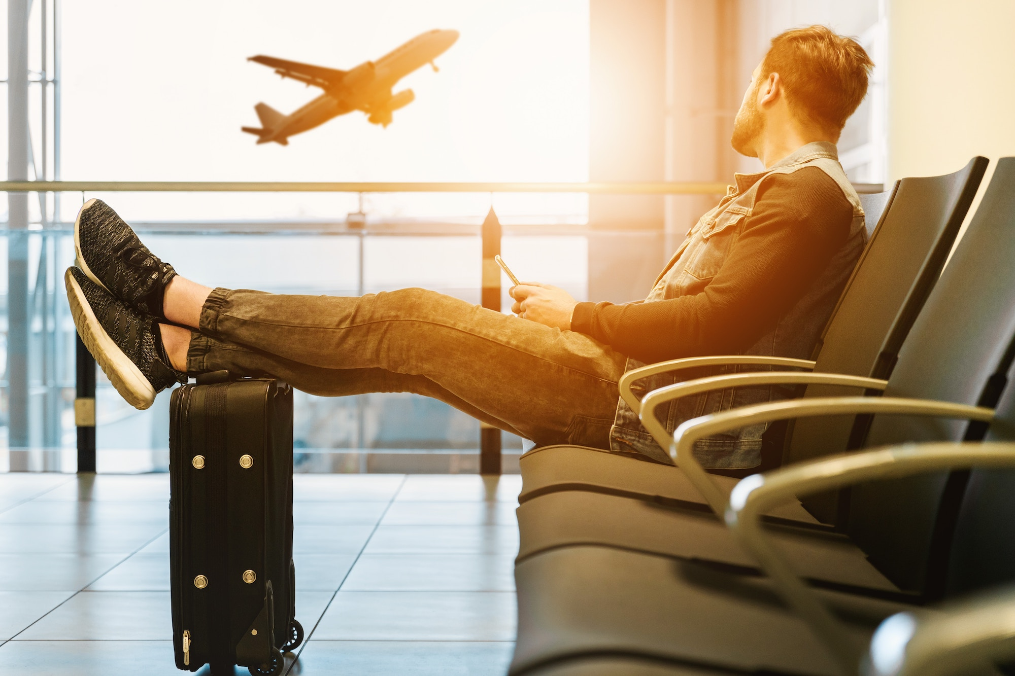 man at airport gate with feet on luggage prepared with travel health